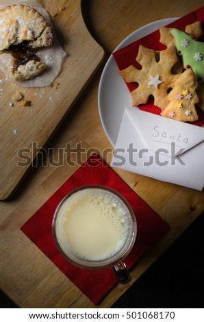 Biscuits (cookies), milk and mince pie left out on wooden table for Santa Claus, with envelope containing wish list.  Mince pie is broken open as though partially eaten.