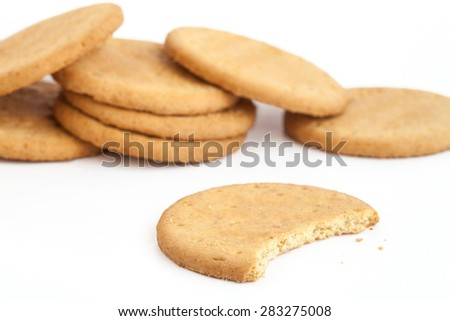 BISCUITS - Delicious wheat round biscuits with a few crumbs isolated on white - stock photo