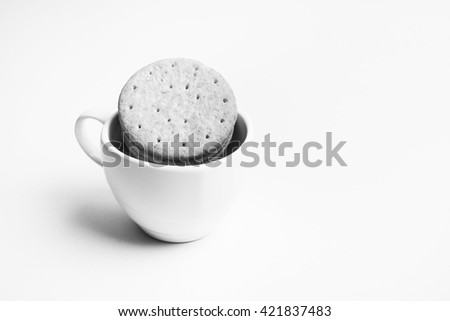 Biscuits in coffee cup on white background