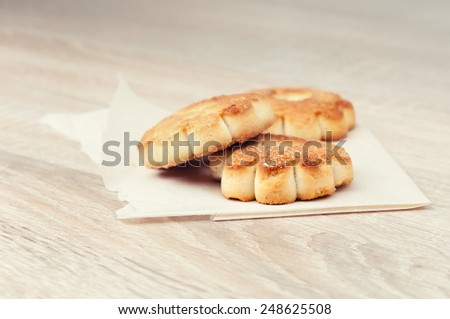 Biscuits wrapped in paper on a wooden table. - stock photo