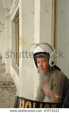 BISHKEK, KYRGYZSTAN - APRIL 7: Young boy hides behind a stolen riot shield on April 7, 2010 in Bishkek, Kyrgyzstan. He his protecting himself from sniper fire as the surrounding buildings burn.