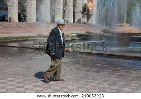 BISHKEK, KYRGYZSTAN - MAY 02, 2014: Elderly asian man walking on Ala-Too Square. Bishkek formerly  Frunze, is the capital and the largest city of the Kyrgyz Republic.  The population - 900,000 people