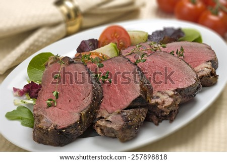 Bison Tenderloin on white plate setting with salad garnishes - stock photo