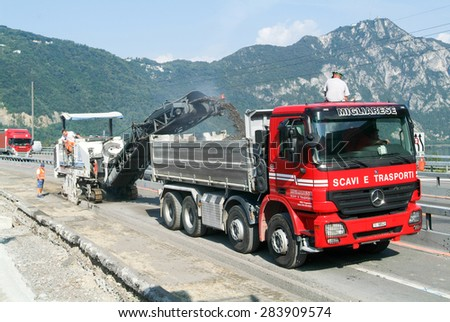Bissone, Switzerland - 16 September 2007: Workers and vehicles during the road milling of the highway at Bissone on Switzerland - stock photo