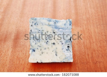 bit of aged french blue roquefort or cheese on wooden table - stock photo