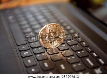 Bitcoin physical coin symbol on black keyboard