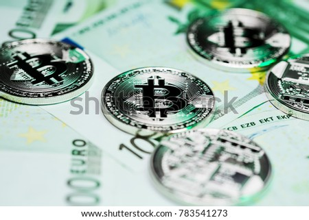 Bitcoins pile on a hundred euro bills/banknotes. Conceptual closeup image showing the connection of the new cryptocurrency and euro markets.