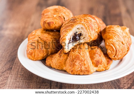 bite croissants with chocolate on a white plate, french kitchen, breakfast - stock photo