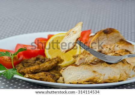 Bite from fried boneless and skinless Rosemary Lemon Chicken breast on tip of fork in selective focus with reds yellows and green in soft focus background. - stock photo