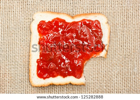bite out of a slice of bread with strawberry jam on sacking background
