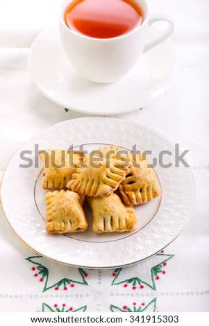 Bite size pastries on plate and cup of tea