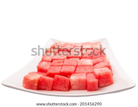 Bite size watermelon on a white plate over white background - stock photo