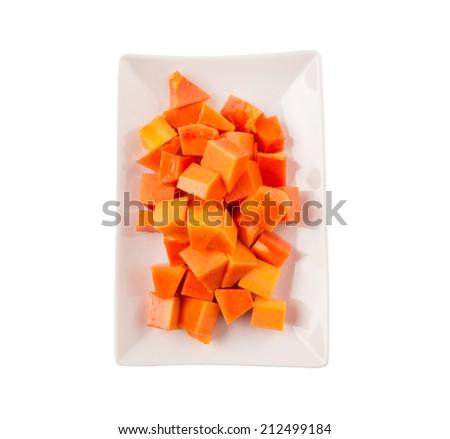 Bite sized papaya fruit on a white plate over white background - stock photo