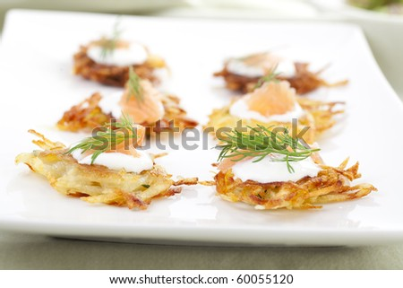 Bite sized potato rosti appetizer topped with fresh sour cream, smoked salmon and dill. - stock photo