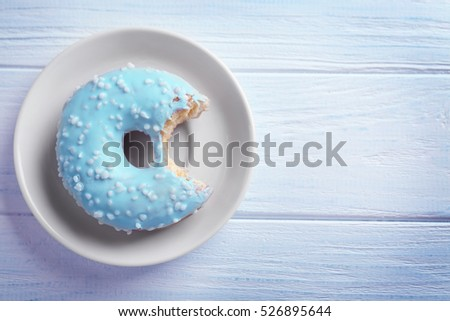 Bitten donut on plate on wooden background
