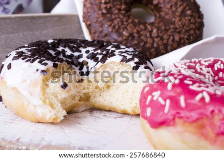 bitten donuts with icing on a white napkin - stock photo