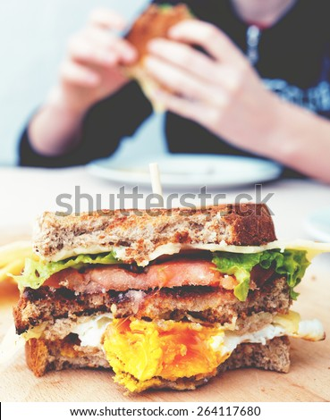 Bitten egg sandwich and person eating in the background. Image filtered - stock photo