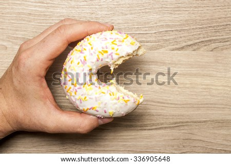 Bitten glazed donut with toppings, in the man`s hand.