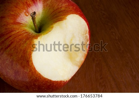 Bitten off apple on a brown wooden surface - stock photo