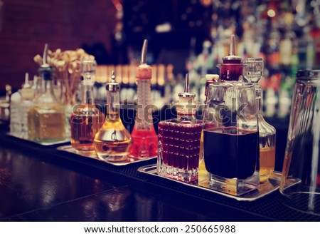 Bitters and infusions on bar counter, bar bottles in blurred background, toned image - stock photo