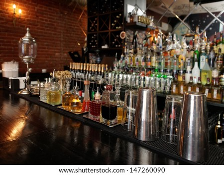 Bitters and infusions on bar counter with blurred bottles in background - stock photo