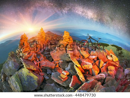 Bivouac extreme riders on the Carpathian Gorgan through peaks and Synyak Hamster on a background of the night of the valley with fog and lights of the city under the stars of the Galaxy - stock photo