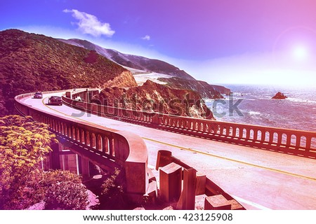 Bixby Creek Bridge on Highway #1 at the US West Coast traveling south to Los Angeles, Big Sur Area - Picture in a dreamy look with purple fall color look - stock photo