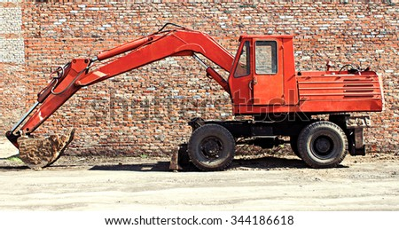 BIYSK, RUSSIA - MAY 29, 2010: Old red excavator with bucket against the background of a brick wall - stock photo