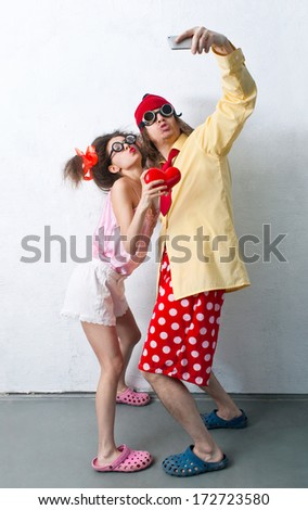 Bizarre couple in love is photographed on a mobile phone - stock photo