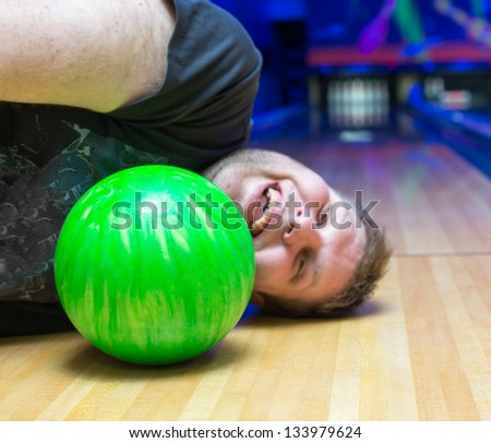 Bizarre drunk man lying on bowling alley - stock photo