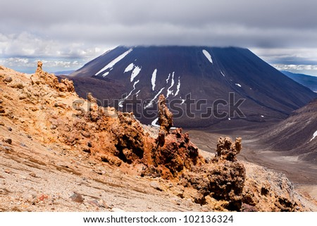 Bizarre lava sculptures in front of active volcano cone of Mount Ngauruhoe as seen from Mount Tongariro in Tongariro National Park, North Island of New Zealand - stock photo