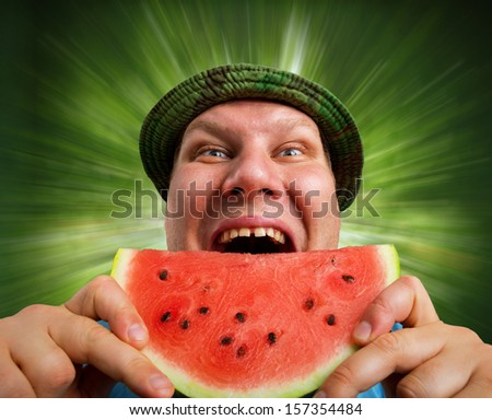 Bizarre man eating watermelon outdoors in summer - stock photo