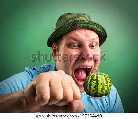 Bizarre man preparing to eat small watermelon on spoon - stock photo