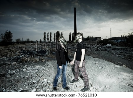 Bizarre portrait of romantic couple with gas masks - stock photo