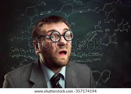 Bizarre professor in glasses thinking over chemical formulas on blackboard - stock photo