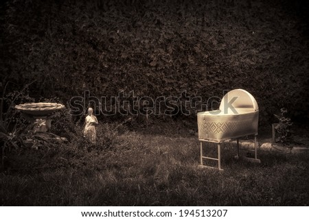 Bizarre, vintage looking photo of a creepy, spooky baby cradle in an overgrown garden.