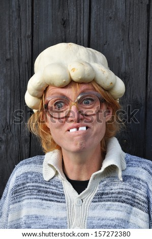 Bizarre woman with a pumpkin on her head. - stock photo