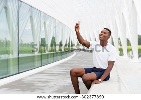 Black, African American college student smiling and taking a selfie with mobile phone on university campus - stock photo