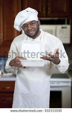 Black African American male chef holding a takeout box - stock photo