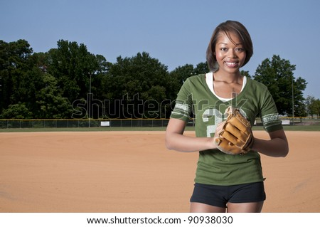 Black African American woman playing baseball at a community park - stock photo