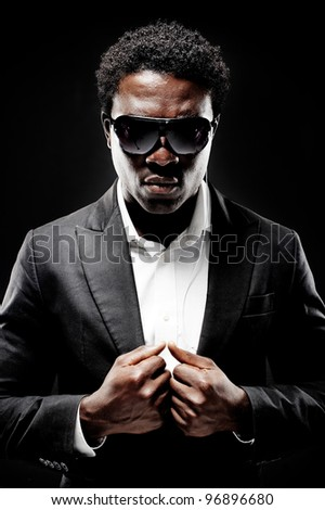 Black african bodyguard or secret agent on a dark background with dramatic lighting gesture towards camera wearing a suit - stock photo
