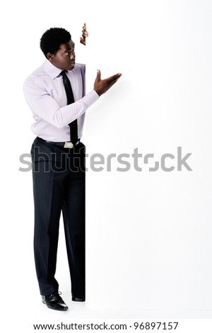 Black african businessman standing with a blank empty board providing copyspace for any advertising material.