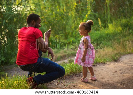 Black African father takes photo of his daughter with by means of mobile phone.
