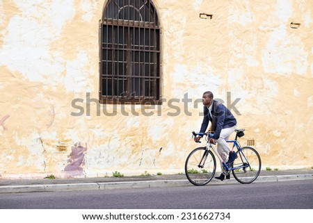 Black african mad riding bicycle in urban city commuting with speed and hipster trendy transportation - stock photo