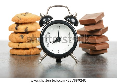 Black alarm clock and sweets - stock photo