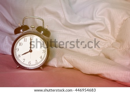 Black alarm clock on the bed with sunrise, wake up concept, vintage and retro style
