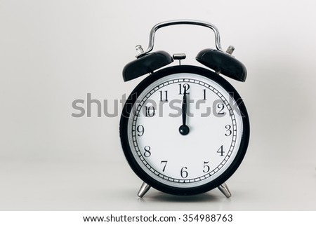 Black alarm clock showing midnight or midday