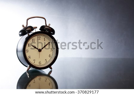 Black alarm clock with reverberation on dark background