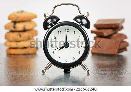 Black alarm clock with sweets - stock photo