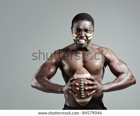 Black american football sportsman gripping a ball in studio - stock photo